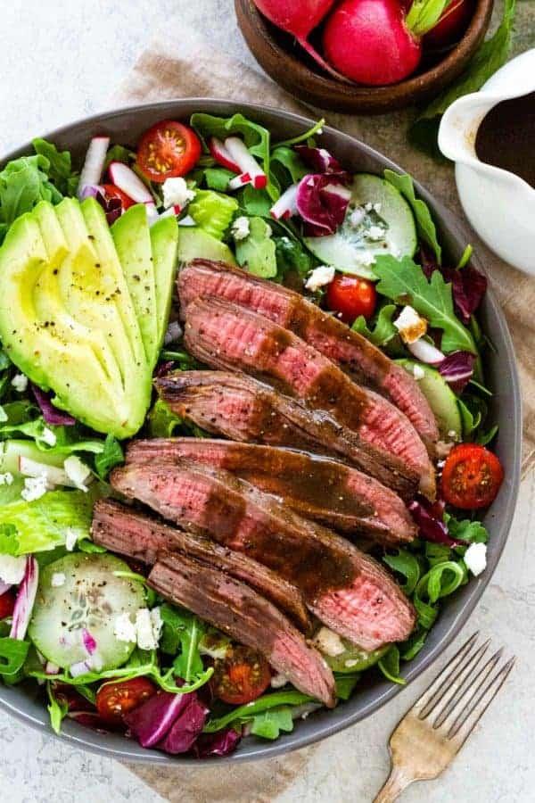 Steak salad with fresh veggies and dressing plus sliced avocado