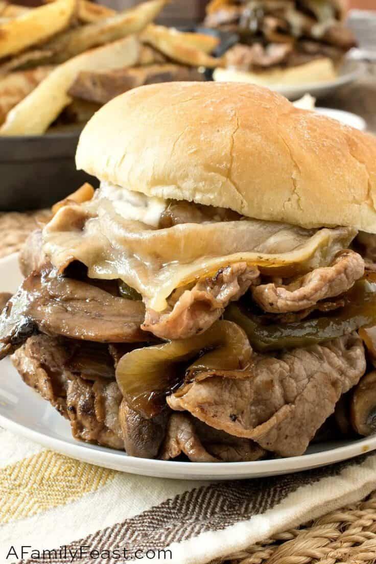 steak sandwich on white plate close up on white bun