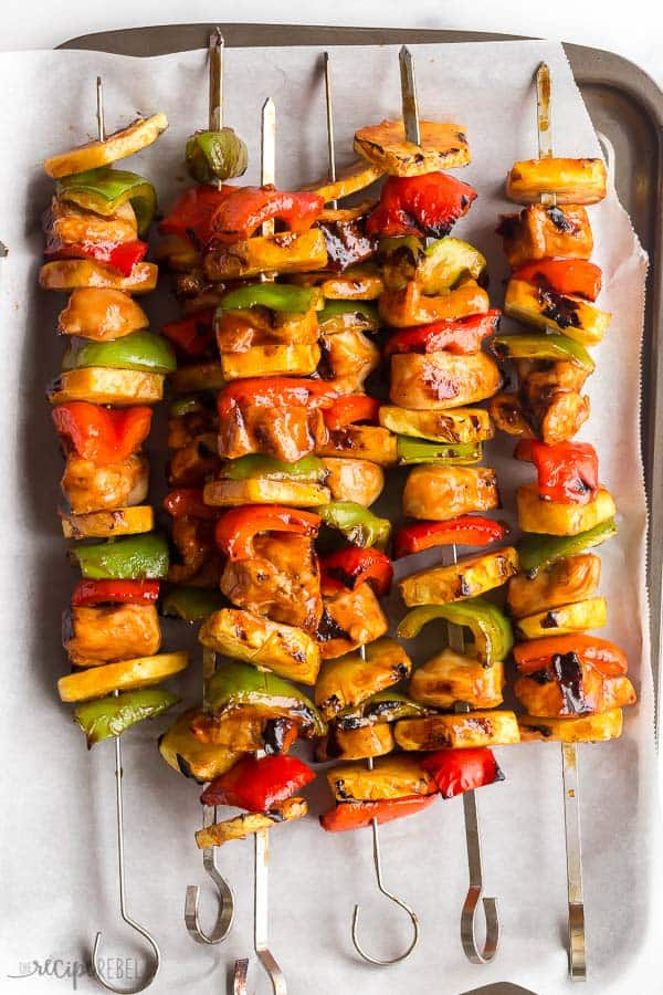 hawaiian chicken kabobs cooked with pineapples and peppers on sheet pan