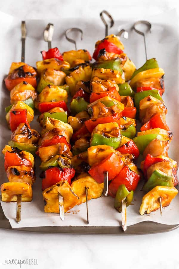 hawaiian chicken kabobs close up on skewers with pineapples and peppers