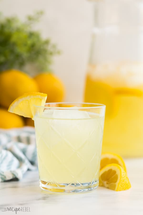 glass of lemonade with lemon wedges and lemons in the background