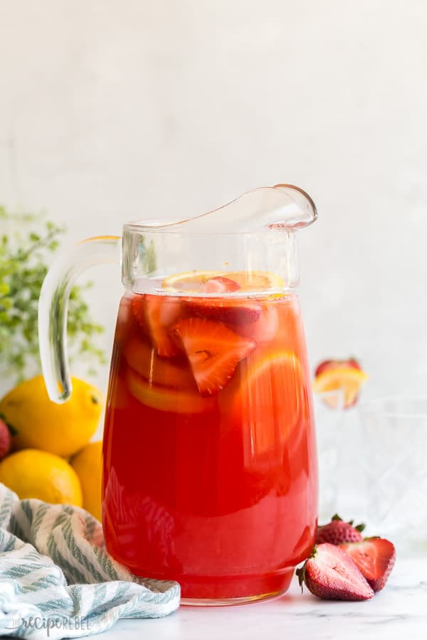 strawberry lemonade in large glass pitcher with lemon slices and strawberries