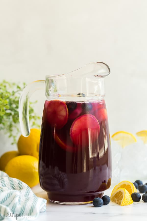 blueberry lemonade with lemon slices and blueberries in glass pitcher