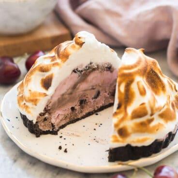baked alaska tart on white plate cut in half to reveal black jack cherry yogurt