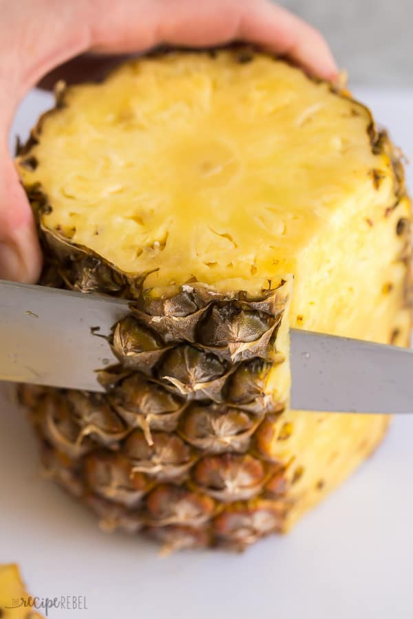 cut the sides off the pineapple with a sharp knife on a white cutting board
