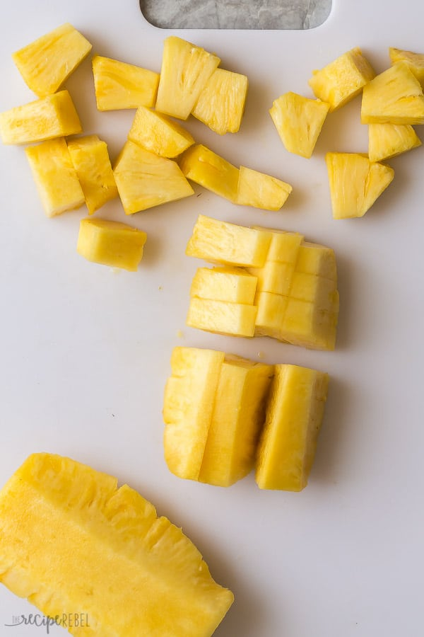 cutting a pineapple on a white cutting board with some pineapple spears and some pineapple chunks