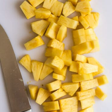 pineapple chunks on a white cutting board with knife