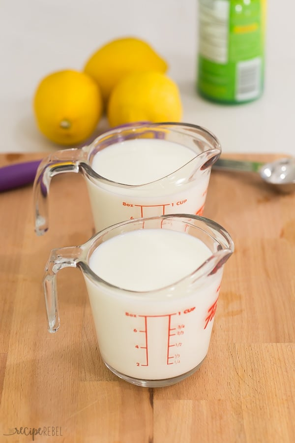 milk in two one cup measuring cups on a wooden cutting board with lemons and lemon juice in the background