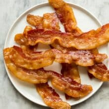 crispy oven baked bacon on white plate on grey marble background overhead
