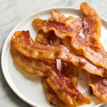 crispy oven bacon on white plate on grey marble background