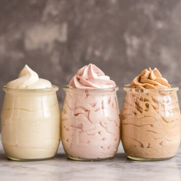 homemade whipped cream recipe 3 flavors in small clear jars against grey background