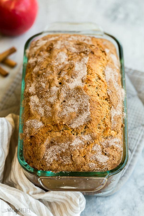 apple bread in glass loaf pan with cinnamon sugar on top