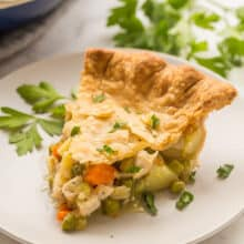 chicken pot pie slice on grey plate with fresh parsley