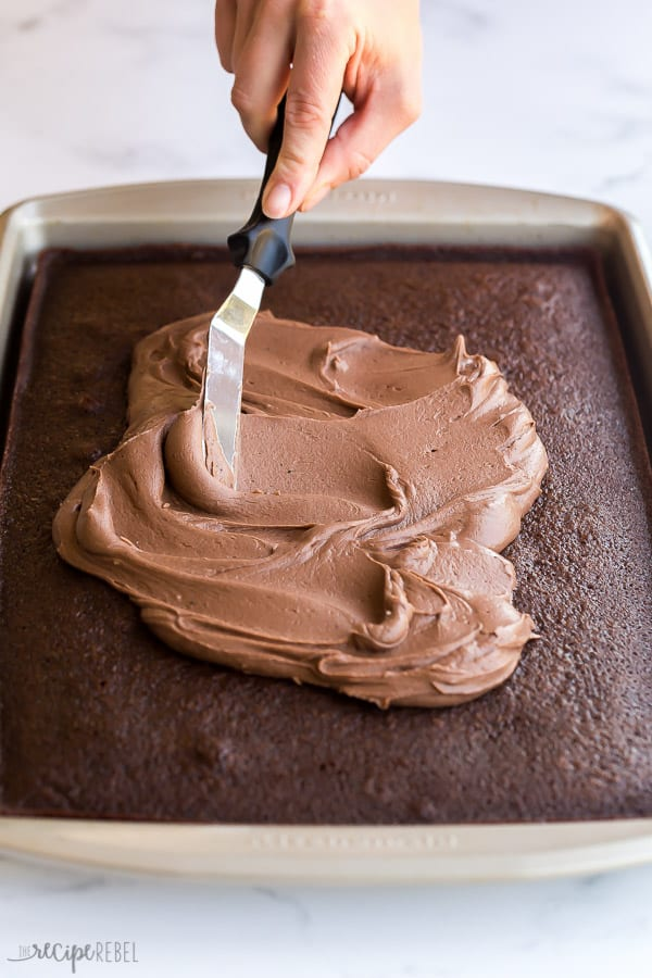 chocolate frosting going on chocolate sheet cake in pan