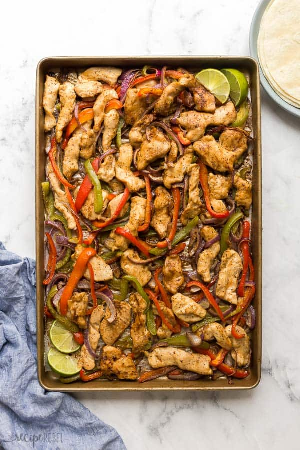 overhead image of a sheet pan with cooked chicken strips bell peppers and onions