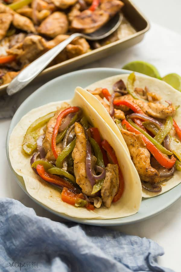 sheet pan chicken fajitas on two flour tortillas on plate