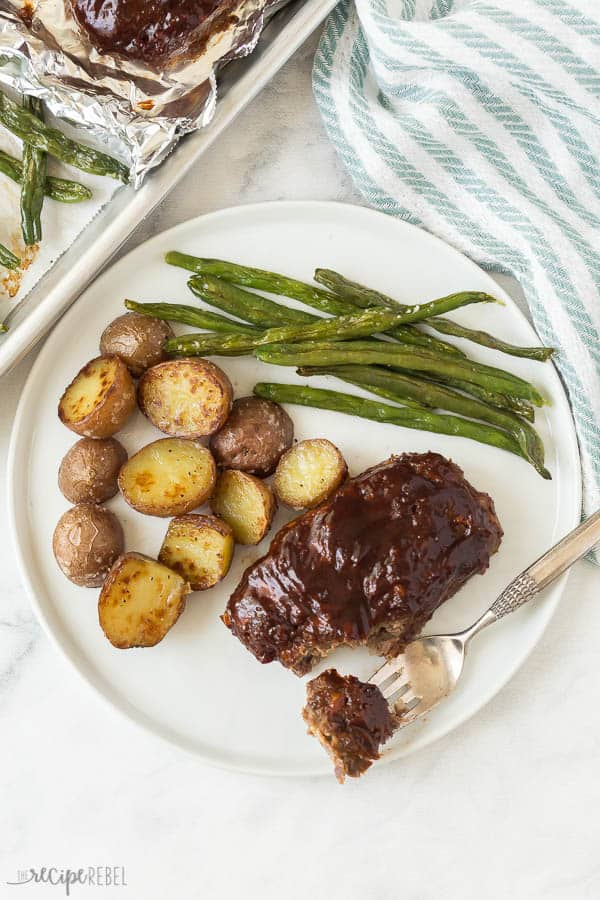 white plate with mini meatloaf roasted potatoes and green beans with fork taking a bite