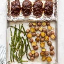 overhead image of four mini meatloaves on sheet pan with potatoes and green beans