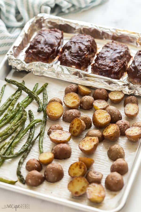 sheet pan on an angle with green beans potatoes and mini meatloaves
