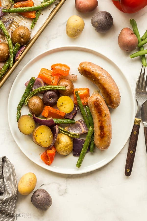 white plate with two sausages and potatoes red pepper and green beans