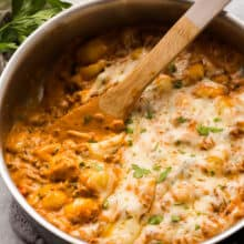 italian sausage gnocchi skillet with wooden spoon scooping