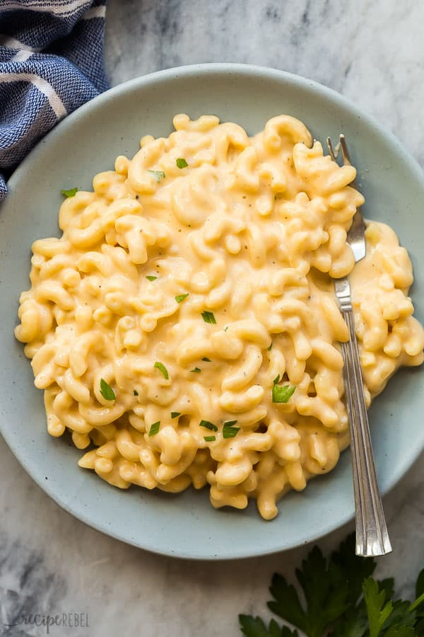mac and cheese on grey plate with fork stuck in