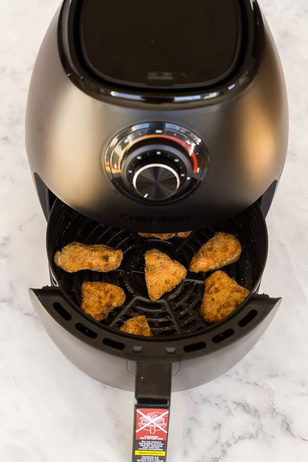 air fryer basket coming out to reveal crispy turkey nuggets