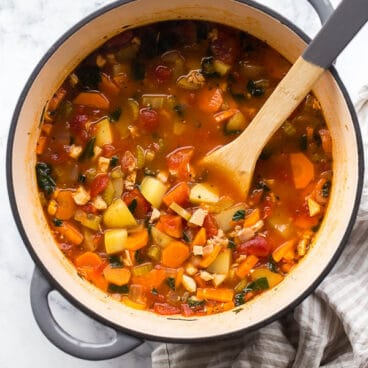 overhead image of pot of soup with wooden spoon stuck in