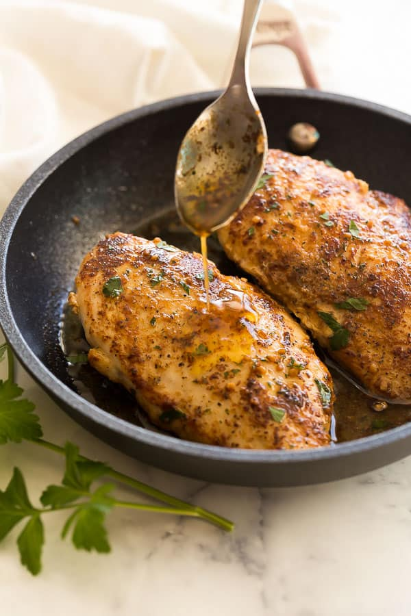 chicken breasts being drizzled with garlic butter sauce in pan