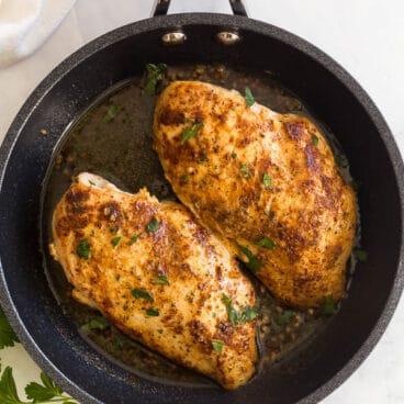overhead image of pan fried chicken breasts in black ninja pan