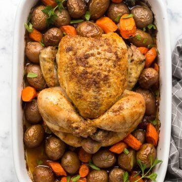 overhead image of roast chicken and vegetables in white baking dish
