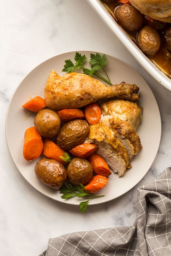 plate of chicken breast and drumstick with potatoes and carrots