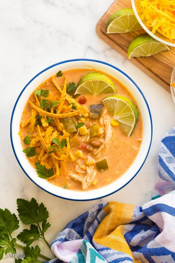 creamy chicken taco soup in bowl with tortilla strips and lime wedges