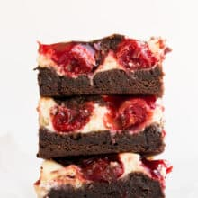 stack of three cherry cheesecake brownies on white background