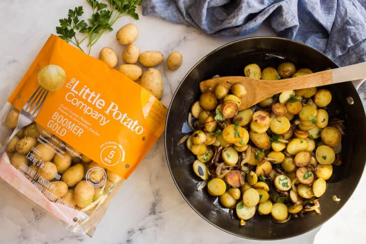 overhead image of potatoes in skillet beside a bag of little potatoes