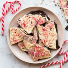 broken wedges of peppermint bark in a bowl with candy canes
