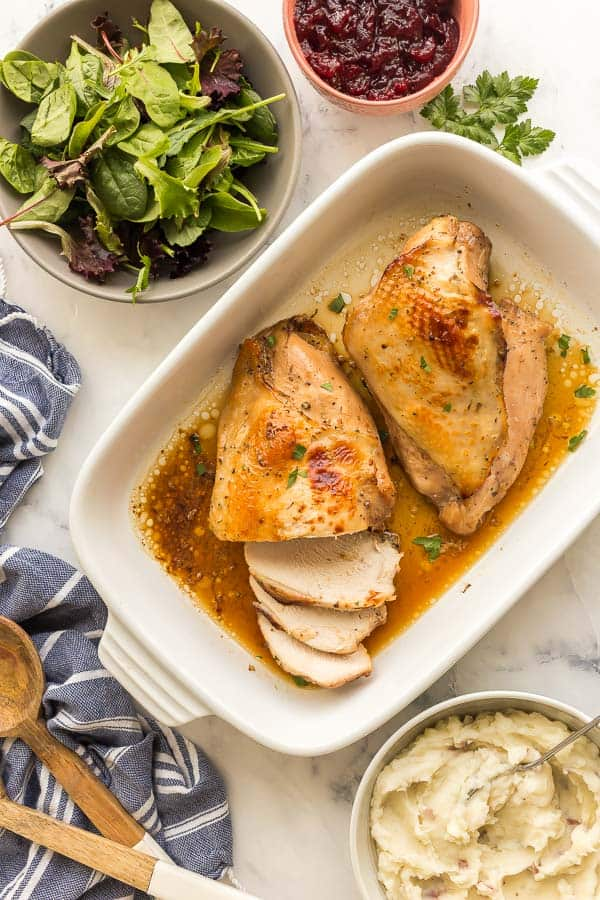 overhead image of roast turkey breast with salad and mashed potatoes