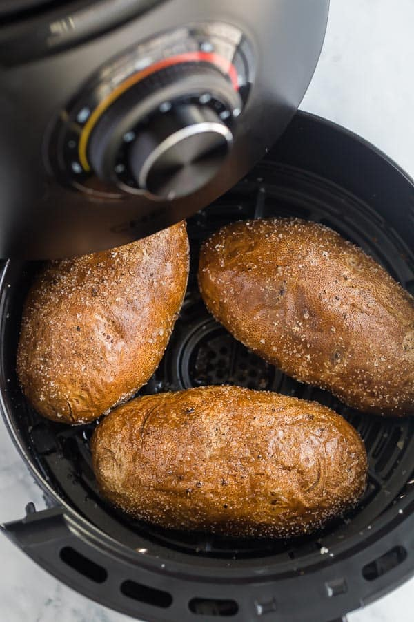 air fryer basked being pulled out of air fryer with potatoes in it