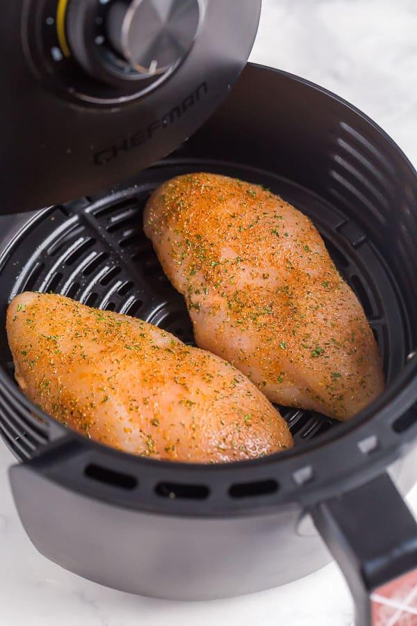 raw chicken breasts with seasoning in air fryer basket