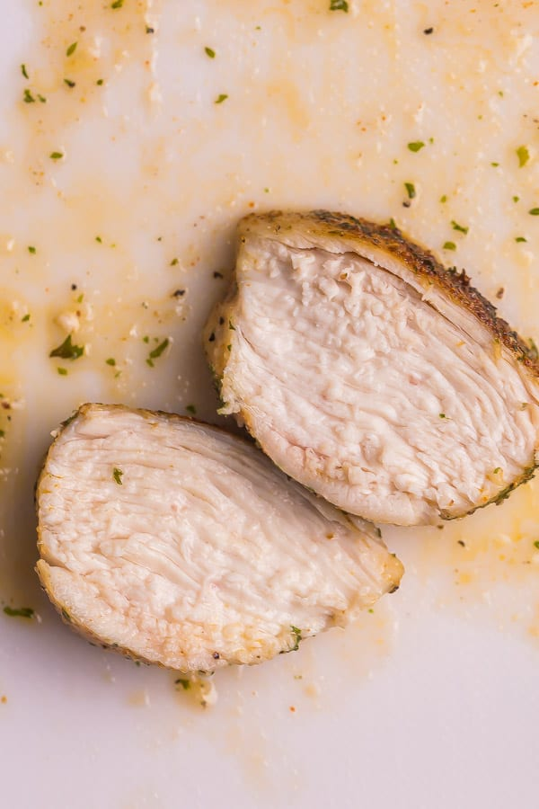 two slices of air fryer chicken breast on cutting board