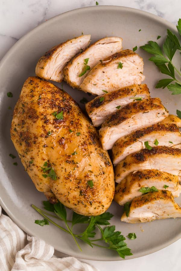air fryer chicken breast one whole and one sliced on plate
