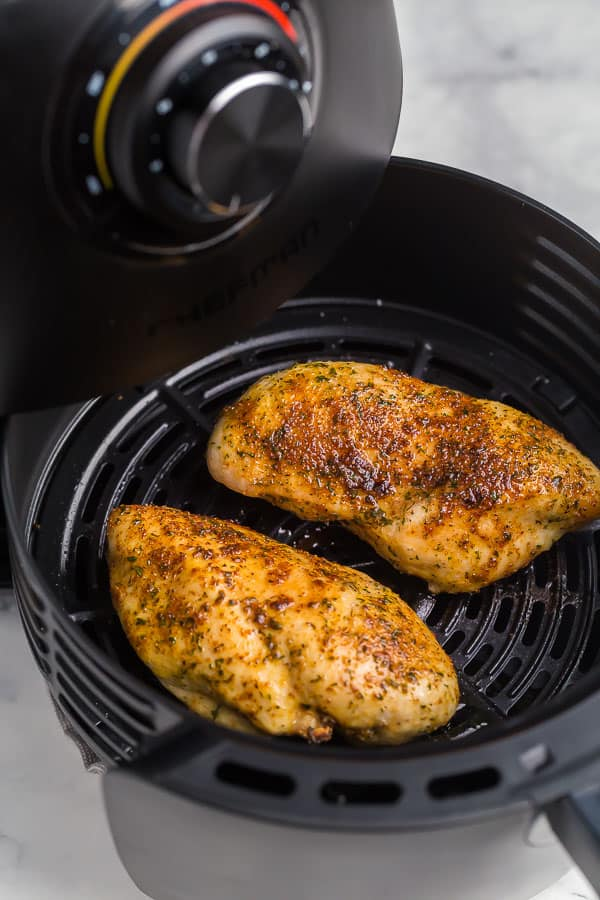 basket being pulled out of air fryer with chicken breast inside