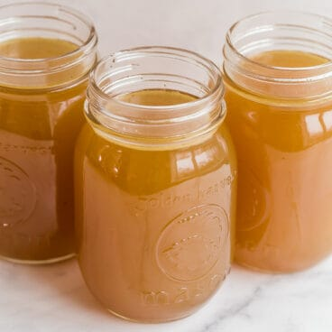 three jars of bone broth on white background
