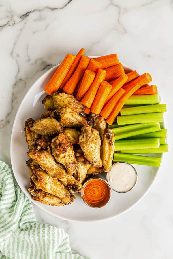 overhead image of plate of chicken wings with carrots and celery
