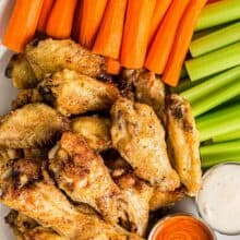 overhead image of cooked chicken wings with vegetables