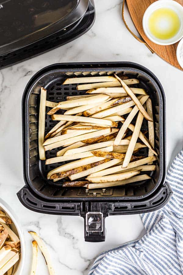 uncooked potatoes in air fryer basket