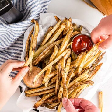 overhead image of hands grabbing air fryer french fries