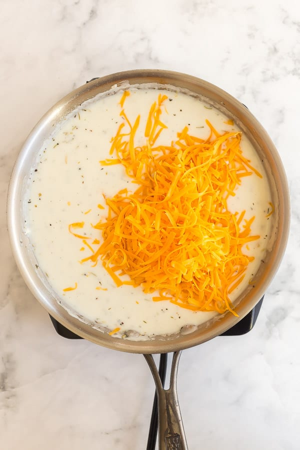 cheddar cheese being added to white sauce