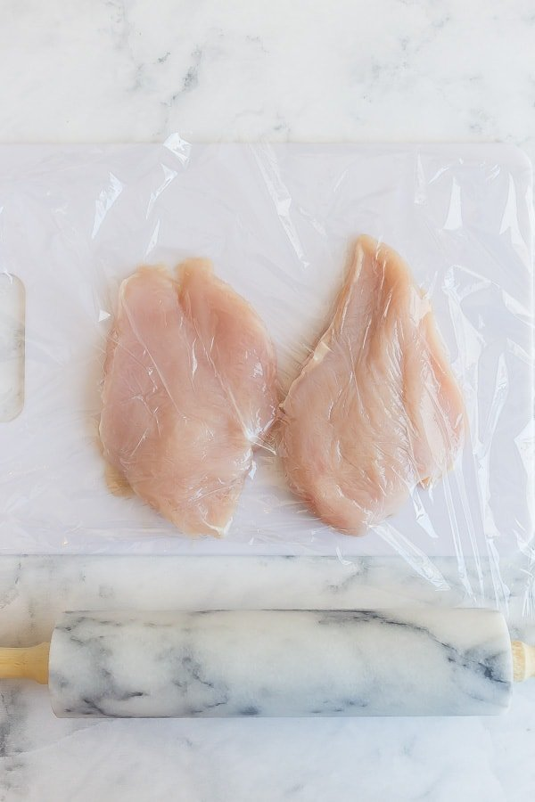 raw chicken breasts with plastic wrap over and rolling pin