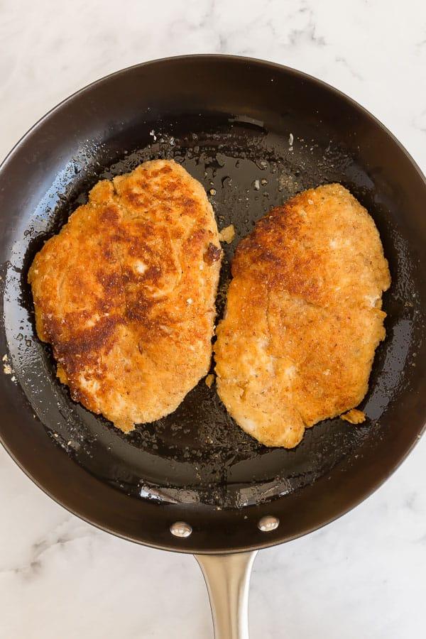 crispy browned chicken breasts in black pan